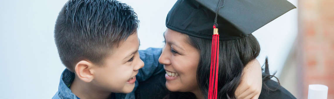 Woman smiling in graduation gown with her arm around her son