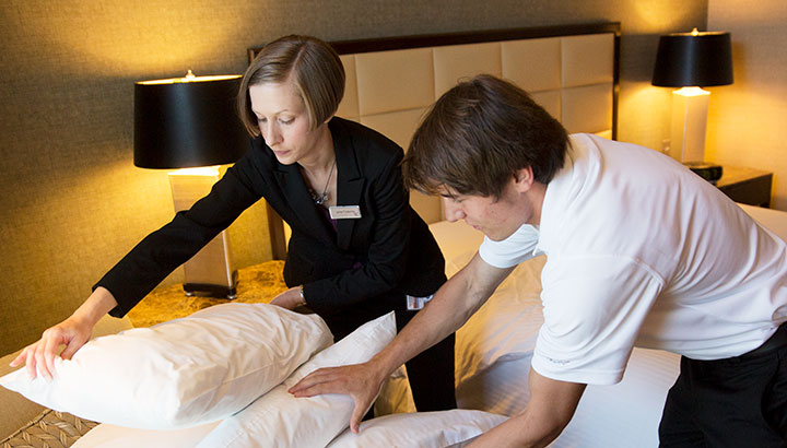 Hotel workers preparing a bed