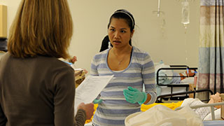 student in the mock nursing lab learning from an instructor