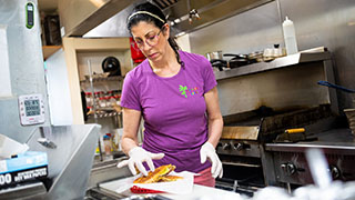 COD grad working in the kitchen she owns