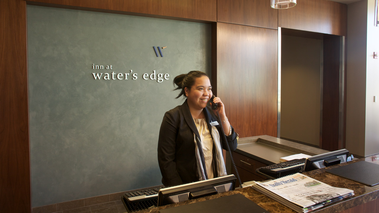Receptionist talking on phone at hotel front desk