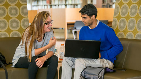 Two students working together on a computer