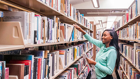 Student getting book off library shelf