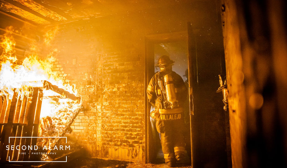 A firefighter extinguishing a fire in a barn that caught fire