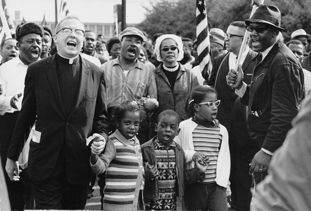 Civil Rights Movement Co-Founder Dr. Ralph David Abernathy and his wife Mrs. Juanita Abernathy follow with Dr. and Mrs. Martin Luther King as the Abernathy children march on the front line, leading the SELMA TO MONTGOMERY MARCH in 1965 (Public Domain)